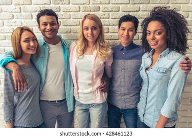Beautiful young people of different nationalities are looking at camera and smiling, standing against white brick wall