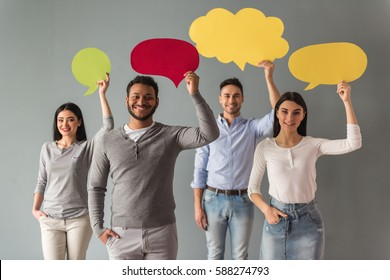 Beautiful young people are holding speech bubbles, looking at camera and smiling, on gray background