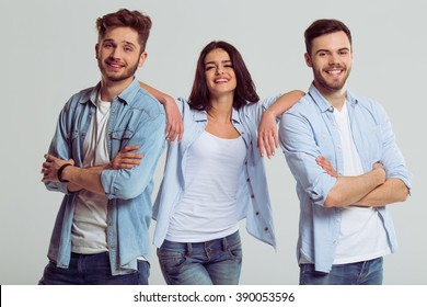 Beautiful young people in jeans are looking at camera and smiling, on a gray background. Woman is leaning on men
