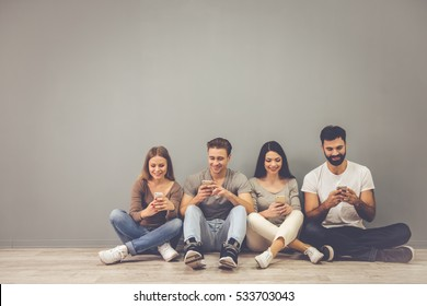 Beautiful young people are using smartphones and smiling while sitting on the floor