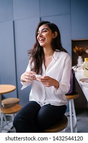 A beautiful, young, and photogenic Indian Asian woman laughs out loud with mirth and amusement. She is casually dressed and sitting in a coffee shop on her own on a weekend morning.