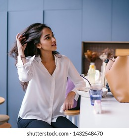 A beautiful, young, and photogenic Indian Asian woman smiles as she relaxes on her own in a coffee shop on the weekend. She is casually and comfortably dressed.