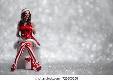 Beautiful young pin-up girl in santa dress unwrapping a christmas present on glitter bokeh background