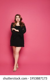 A beautiful young plump woman with makeup in pin-up style wearing black short dress posing against a pink background
