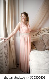 Beautiful young plump woman standing near a bed.