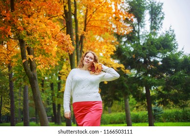 beautiful young plus size model with long curly hair in the autumn park