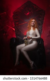 Beautiful Young plus size red hair woman as seductive temptress. halloween portrait of evil curvy woman in skin color outfit on black gothic throne in the dark with red light.
