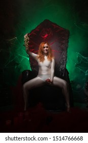 Beautiful Young plus size red hair woman as seductive temptress. halloween portrait of evil curvy woman in skin color outfit on black gothic throne in the dark in green light.