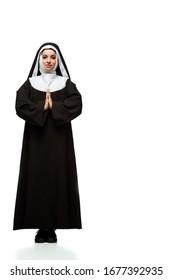 beautiful young praying nun standing on white