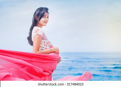 beautiful young pregnant asian woman on a beach