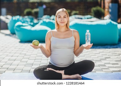 Beautiful young pregnant girl is training yoga in the lotus position in the fresh air, in one hand, holds an apple in a second bottle of water. Healthy Lifestyle.