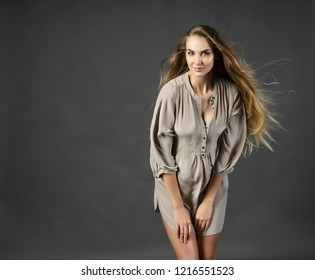 Beautiful young pregnant woman blonde, wearing a short light gray dress with her hair  hair fluttering in the wind. Gray background. Maternity, lifestyle. Copy space.