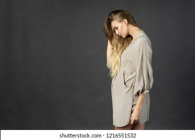 Beautiful young pregnant woman blonde, wearing a short light gray dress, stands sideways and touches her hair with her hand. Gray background. Maternity, lifestyle. Commercial design. Copy space.