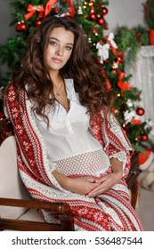 Beautiful young pregnant woman at Christmas home cozy portrait. Happy winter pregnancy. Smiling indian pregnant woman at home at New Year tree. Pregnant indian woman.