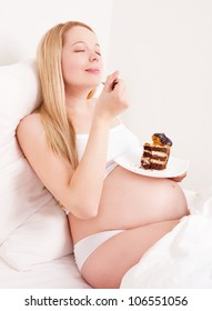 beautiful young pregnant woman eating cake in bed at home smiling