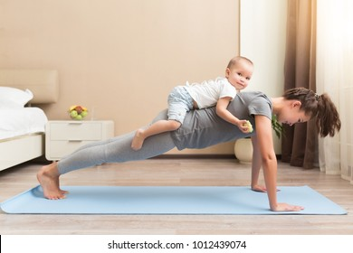 Beautiful young pregnant woman and her two years old little toddler son are smiling while doing yoga exercise together at home on the floor on blue fitness mat. Healthy pregnancy lifestyle concept