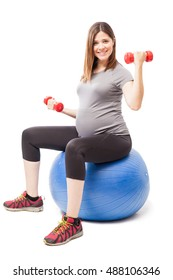 Beautiful young pregnant woman lifting a couple of dumbbells while sitting on a stability ball to stay fit during pregnancy