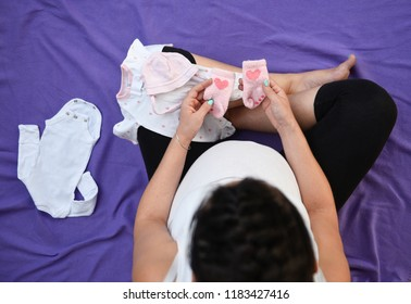A beautiful young pregnant woman looking at baby clothes