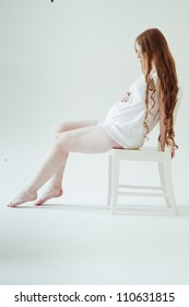 Beautiful young pregnant woman is sitting