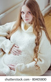 Beautiful young pregnant woman sitting on sofa