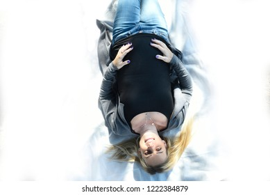 Beautiful young pregnant woman with a smile on her face laying on white blanket, holding her belly