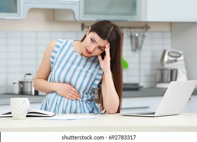 Beautiful young pregnant woman suffering from headache while working with laptop in kitchen
