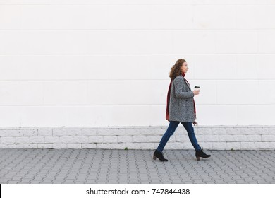 Beautiful young pregnant woman wearing sweater, jeans, grey coat and red scarf walking through the city streets and drinking take away coffee