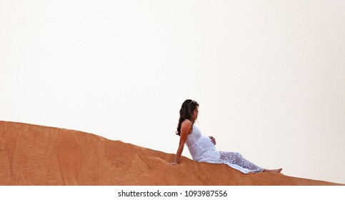 Beautiful Young Pregnant Women, 8 months Pregnant, wearing white lace dress standing in desert sand dune scene