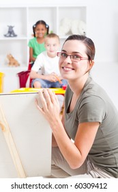 beautiful young preschool teacher teaching in classroom