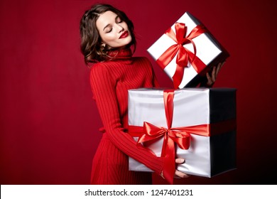 Beautiful young pretty woman with a bright evening make-up of shiny red lipstick on the lips brunette curly hair festive mood knitted red sweater winter Christmas New Year and birthday gift surprise.