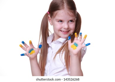 Beautiful young pupil in blue and yellow finger paints as colors of national ukrainian flag