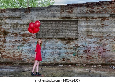 Beautiful young red hair girl in red dress with red helium balloons in hand inside of abandoned place with big ruined brick graffiti wall on background. HDR image