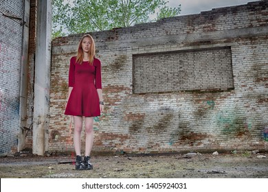 Beautiful young red hair girl in red dress inside of big abandoned ruined industrial building with graffiti on the brick walls