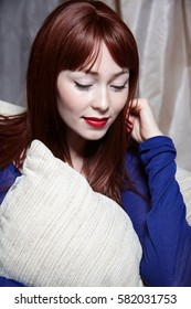 Beautiful young red hair girl portrait with natural make up and red lips in blue clothes and blue jeans in interior