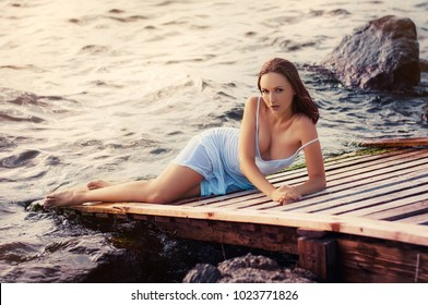 Beautiful young red hair woman in tight white dress with bare feet with wet hair and dress on sea beach at sunset.