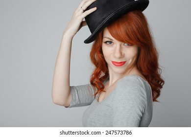 beautiful and young red haired woman in black hat over grey background in studio