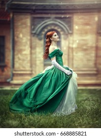 Beautiful, young, red-haired girl in a green medieval dress, climbs the stairs to the castle.