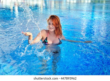 Beautiful young red-haired girl squirting water in the pool