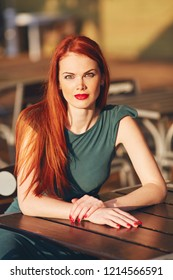 Beautiful young red-haired woman in green dress. Outdoor lifestyle portrait in sammer cafe