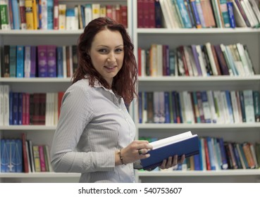Beautiful young redhead girl reading a book in library. Doing research, thinking. Bookshelves with lots of books in background.