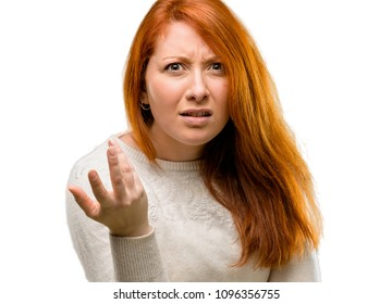 Beautiful young redhead woman irritated and angry expressing negative emotion, annoyed with someone isolated over white background