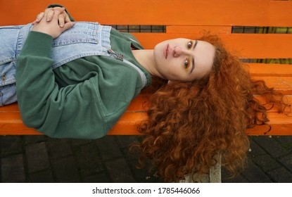 Beautiful young redhead woman lying on orange bench in sunny autumn day. side view. cute serious ginger woman lying outdoors. Looking at camera. autumn season.