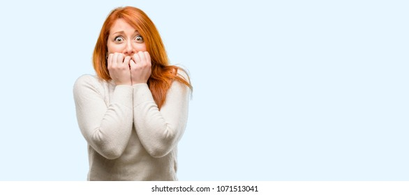 Beautiful young redhead woman terrified and nervous expressing anxiety and panic gesture, overwhelmed isolated over blue background