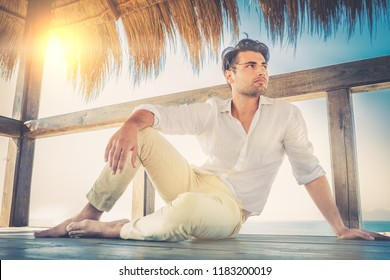 Beautiful young relaxed man in a small wooden deck. Strong summer warm lights. Trendy haircut. White shirt and beige trousers.