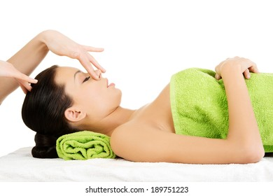 Beautiful young relaxed woman enjoy receiving face massage therapy at spa saloon