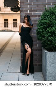 Beautiful young retro woman in luxurious black glamorous evening chic dress. Leather fashionable harness belt on sexy leg. Elegant long gloves. Girl fashion model posing. Vintage buildings background
