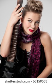 Beautiful young rock girl in purple stocking with black electric guitar sitting on white fur sofa