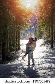 beautiful young romantic couple kissing in a stunning park covered by snow during winter.  two lovers kissing in San valentine's day