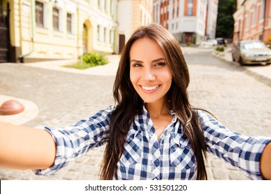 Beautiful young runette with beaming smile making selfie