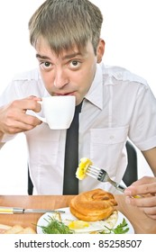 beautiful young Russian guy sitting at the table and eat a muffin, isolated over white